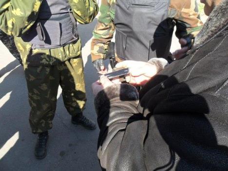 Часть нападавших была одета в форму и бронежилеты. На этом фото видна кобура с пистолетом у одного из них
